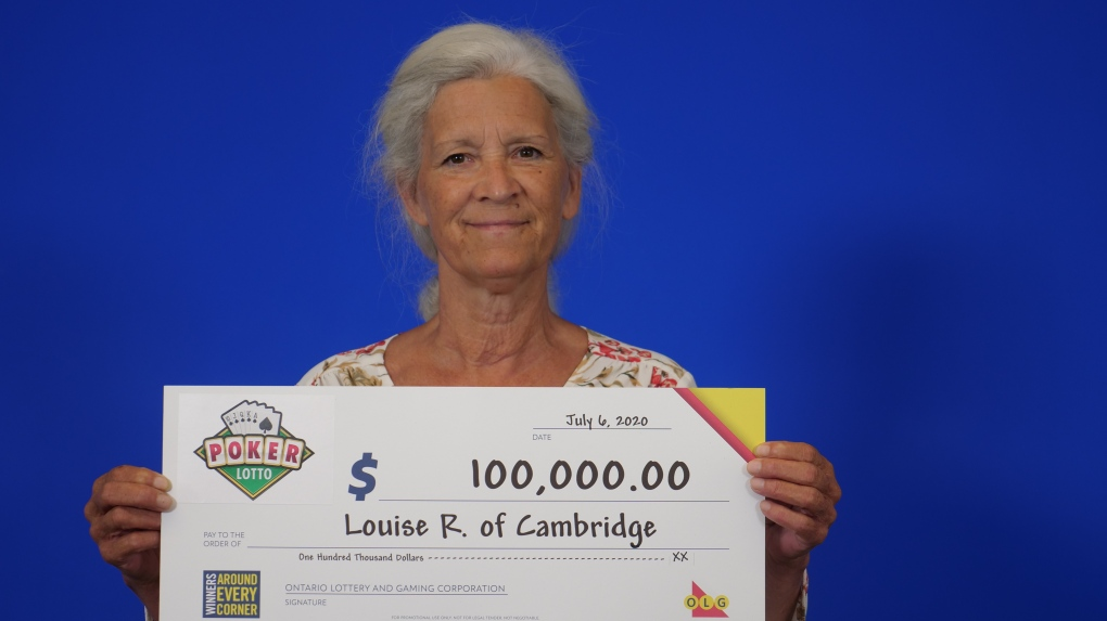 a woman holds a large cheque for $100,000