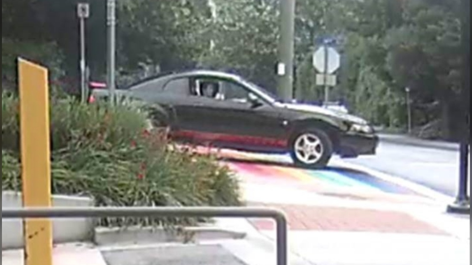 Police have released surveillance images after tire markings were found on the rainbow crosswalk in West Vancouver. (West Vancouver police)