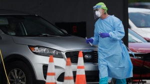 A healthcare worker walks around a car to test a passenger at a drive-through COVID-19 testing site outside Hard Rock Stadium, Wednesday, July 8, 2020, in Miami Gardens, Fla. Florida is one of the U.S.'s hot spots for coronavirus. Almost 10,000 confirmed cases were added Wednesday, bringing its total since March 1 to nearly 224,000. Almost 4,000 people have died, including 48 reported by the state Wednesday. (AP Photo/Wilfredo Lee)