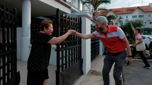 Lee Hsien Yang, the estranged brother of Singapore Prime Minister Lee Hsien Loong, wears a face mask while doing a fist bump with a female resident at a private estate in Jurong West during a walkabout campaign for the opposition Progress Singapore Party in Singapore on July 8, 2020. Singaporeans go to the polls on July 10 in Southeast Asia's first election since the coronavirus pandemic began, with the health crisis and an economic recession expected to bolster Prime Minister Lee's party and extend its unbroken rule. (AP Photo/Ee Ming Toh)