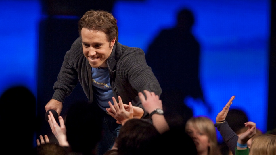 Craig Kielburger founder of the charity Free the Children gets high 5's from the audience at the charity's We Day celebrations in Kitchener, Ontario, February 17, 2011. The Canadian Press/GEOFF ROBINS