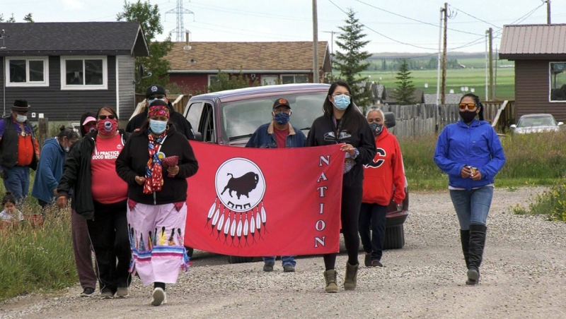 Members of the Piikani Nation form a procession to protest the devastation wrought on their community by an opioid epidemic and the COVID-19 pandemic