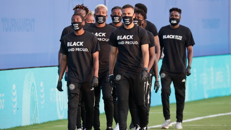 Members of all the MLS soccer teams march around the stadium before a soccer match Wednesday, July 8, 2020, in Kissimmee, Fla., wearing shirts and masks with messages about race. (AP Photo/John Raoux)