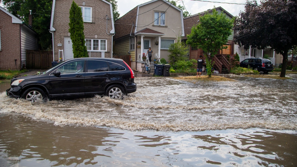 A car drives through a flooded Louvain Street after a severe thunderstorm caused localized flooding in Toronto on Wednesday, July 8, 2020. THE CANADIAN PRESS/Carlos Osorio
