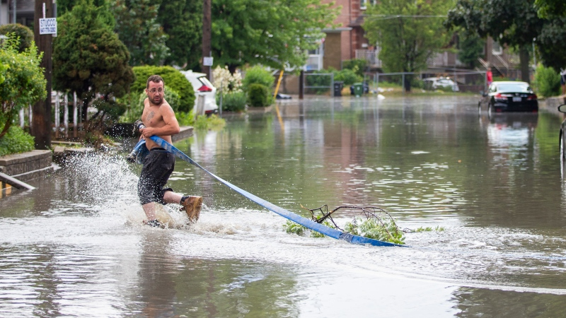 Lucas Silva tries to setup a house to pump water out of his basement apartment on Cordella Avenue after a severe thunderstorm caused localized flooding in Toronto on Wednesday, July 8, 2020. THE CANADIAN PRESS/Carlos Osorio