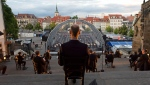 Singers sit apart prior the rehearsal of the Cathedral Steps open air festival (Domstufen-Festspiele) in front of Mariendom (Cathedral of Mary) and St. Severi's Church in Erfurt, Germany, Wednesday, July 8, 2020. (AP Photo/Jens Meyer)