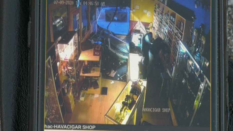 Surveillance video shows a truck smashing into Hav-A-Cigar and two thieves stealing products before fleeing.