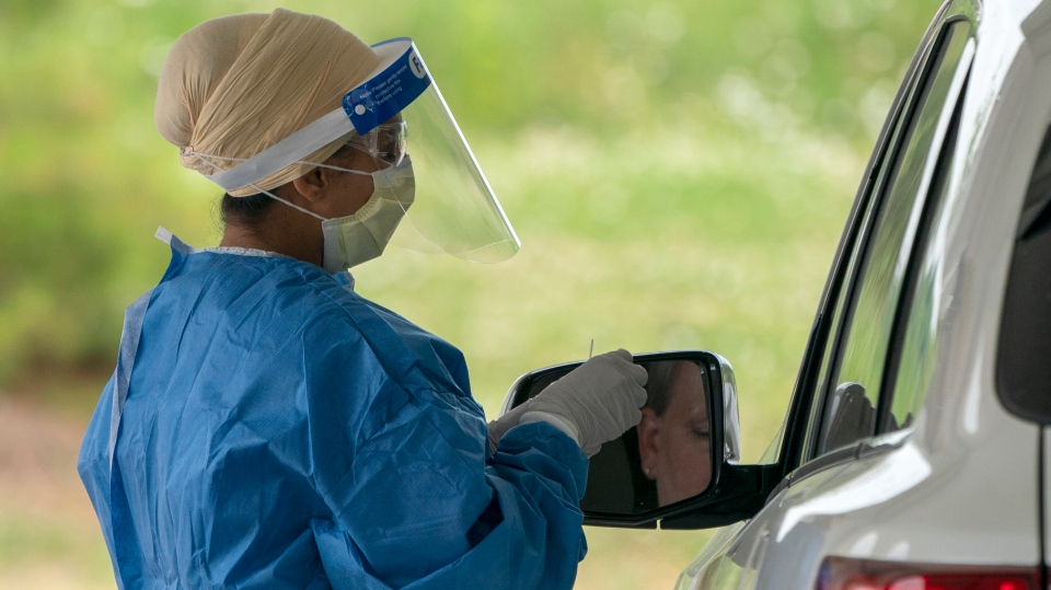 A nurse prepares to do a COVID-19 test at the drive through centre at Etobicoke General Hospital on Monday, June 22, 2020. (Frank Gunn/The Canadian Press)