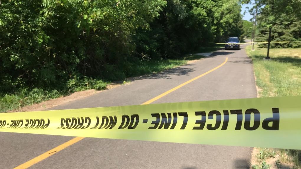 Police line blocks a trail, a cruiser in backgroun