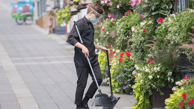 A man wears a face mask and shield as he cleans the sidewalk next to an outdoor terrace in Montreal as the COVID-19 pandemic continues in Canada and around the world. THE CANADIAN PRESS/Graham Hughes