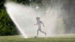 Josephine Young runs through a sprinkler as she takes a break from a bike ride near the Ottawa River on Tuesday July 7, 2020 in Ottawa. (THE CANADIAN PRESS / Adrian Wyld)