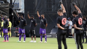 Orlando City players, left, raise their fists in the air in solidarity with other MLS teams before the start of a match in Kissimmee, Fla., on July 8, 2020. (John Raoux / AP)