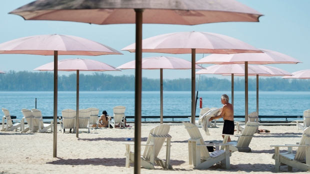 People practice physical distancing as they enjoy the hot weather at Sugar Beach during the COVID-19 pandemic in Toronto on Tuesday, May 26, 2020. (Nathan Denette/The Canadian Press)