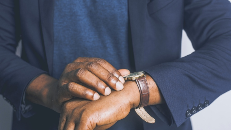 A man checks his watch in this stock image. (Pexels)
