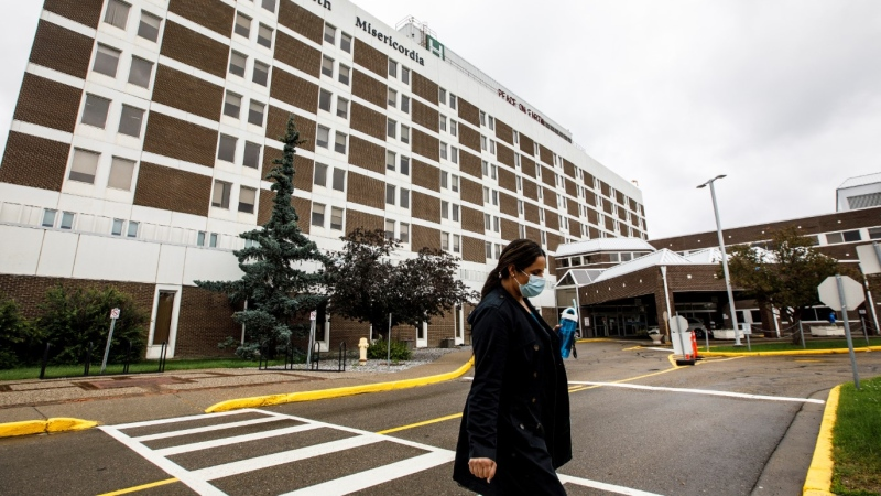 A person wearing a mask walks away from the Misericordia Community Hospital in Edmonton Alta, on Wednesday July 8, 2020. THE CANADIAN PRESS/Jason Franson