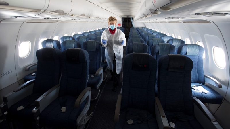 A flight attendant wears personal protective equipment as they walk through the back part of a near empty plane travelling from Calgary to Vancouver, Tuesday, June 9, 2020. (THE CANADIAN PRESS/Jonathan Hayward)
