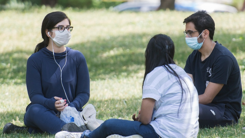 People wear face masks as they gather in a city park on Canada Day in Montreal, Wednesday, July 1 2020, as the COVID-19 pandemic continues in Canada and around the world. Sexologist Jill McDevitt is likening the face mask debate to the condom debate from the past. THE CANADIAN PRESS/Graham Hughes