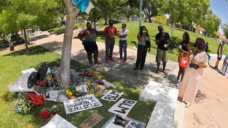 In this Monday, June 15, 2020, file photo, people stand by a memorial as they gather near the site where Robert Fuller was found hanged in Palmdale, Calif. A police investigation confirmed suicide was the cause of death of Fuller, a Black man found hanging from a tree in a Southern California city park last month, authorities said Thursday, July 9, 2020. (AP Photo/Mark J. Terrill, File)