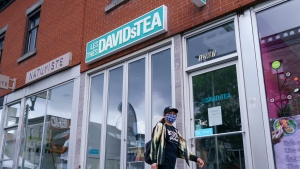A woman wearing a protective mask walks past a closed DavidsTea store in Montreal on Wednesday, July 8, 2020. The Montreal-Based company is seeking court protection from creditors so it can continue operating while it restructures and plans to close a significant number of its stores. THE CANADIAN PRESS/Paul Chiasson