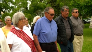 84-year-old John Morrisseau (centre) finishes a walk in protest of the federal government at the grave site of Louis Riel in Saint Boniface, Winnnipeg, Manitoba. (Source: CTV News Winnipeg)