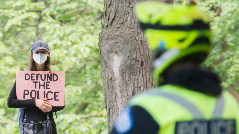 A police officer looks on as a woman holds a 'Defund the Police' sign during a gathering in Mount Royal Park calling for justice for the death of George Floyd and all victims of police brutality in Montreal, Sunday, June 14, 2020. THE CANADIAN PRESS/Graham Hughes