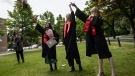 Students toss their caps into the air while posing for family photos after a graduation ceremony at Magee Secondary School in Vancouver, on Thursday, June 11, 2020. THE CANADIAN PRESS/Darryl Dyck