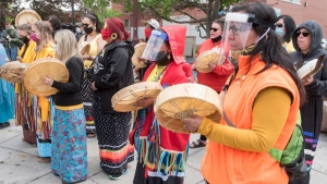 First Nations women in face masks and shields drum during a healing ceremony in town square to honour Chantel Moore in Edmundston, N.B., on Saturday, June 13, 2020. THE CANADIAN PRESS/Stephen MacGillivray