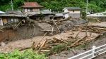 Flood waters carrying mud and debris flows through Takayama city, Gifu prefecture, central Japan Wednesday, July 8, 2020. (Kyodo News via AP)