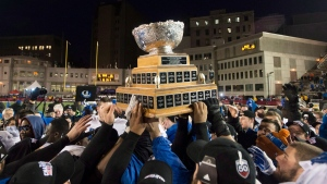 Players from the Montreal Carabins hoist the Vanier Cup after beating the McMaster Marauders in the CIS football final in Montreal on November 29, 2014. (Graham Hughes / THE CANADIAN PRESS)