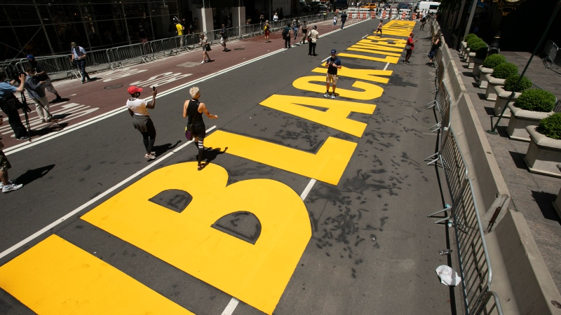 Volunteers walk along a Black Lives Matter mural that was painted on Fifth Avenue in front of Trump Tower, Thursday, July 9, 2020, in New York. (AP Photo/Mark Lennihan)