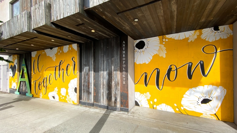 "Jocelyn Wong's mural, featuring white flowers on a bright yellow background with the words ""All together now,"" was displayed for just a few days on the Anthopologie storefront on Granville Street before the store reopened."