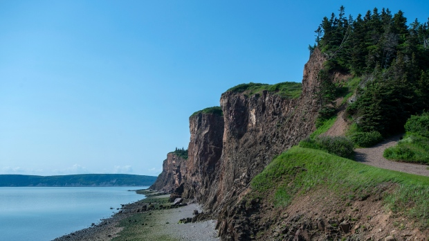 Massive cliffs tower over the shore near the Cape d'Or Lighthouse, near Advocate Harbour, N.S., on Wednesday, July 3, 2019. The Cliffs of Fundy has officially become a UNESCO Global Geopark. (THE CANADIAN PRESS/Andrew Vaughan)