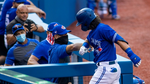 Toronto Blue Jays' Bo Bichette gets an elbow bump from coach Pete Walker after hitting a home run during MLB intrasquad baseball action in Toronto on Thursday, July 9, 2020. THE CANADIAN PRESS/Carlos Osorio