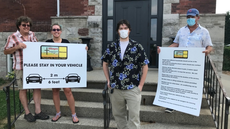 From left, John and Elizabeth Herbert, Pastor Jacob Shaw and David Burghardt stand in Granton, Ont. on Friday, July 10, 2020 with signs to be used at a drive-in church service near Grand Bend, Ont. (Sean Irvine / CTV News)