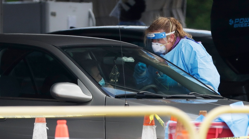 A health care worker prepares to test a driver in line at a drive-thru COVID-19 testing site outside Hard Rock Stadium, Wednesday, July 8, 2020, in Miami Gardens, Fla. (AP Photo/Wilfredo Lee)