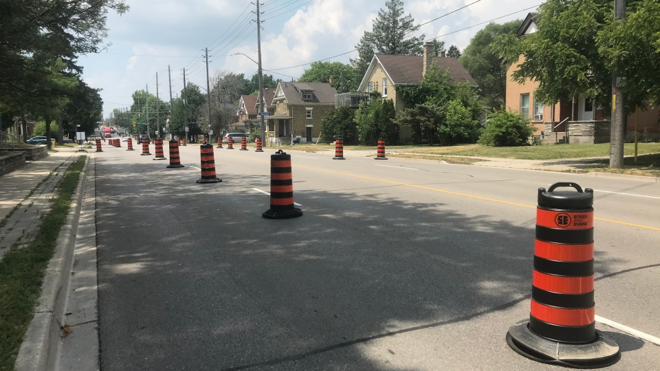 A curbside lane is seen blocked off by barrels in order to provide more space for pedestrians and cyclists. (Heather Senoran / CTV Kitchener)