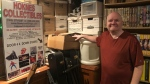 Terry Hocknes stands in front of boxes full of old newspapers and a bookshelf dedicated to his most sought after collection - Saskatoon phone books. (Francois Biber/CTV Saskatoon.)