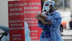 A health care worker carries a stack of clipboards at a COVID-19 testing site sponsored by Community Heath of South Florida at the Martin Luther King, Jr. Clinica Campesina Health Center, during the coronavirus pandemic, Monday, July 6, 2020, in Homestead, Fla. (AP / Lynne Sladky)