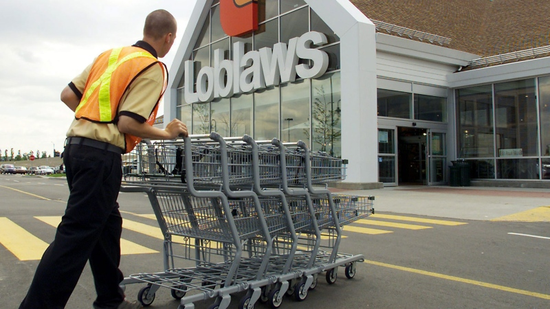 An employee rounds up some grocery carts at the Loblaws store in Brossard, Que. Wednesday, June 7, 2000. The store is the object of a court battle to determine whether it must be torn down due to alleged zoning law violations.(CP PHOTO/Ryan Remiorz)