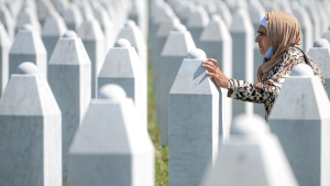A woman touches a grave stone in Potocari, near Srebrenica, Bosnia, Saturday, July 11, 2020. Nine newly found and identified men and boys were laid to rest as Bosnians commemorate 25 years since more than 8,000 Bosnian Muslims perished in 10 days of slaughter, after Srebrenica was overrun by Bosnian Serb forces during the closing months of the country's 1992-95 fratricidal war, in Europe's worst post-WWII massacre. (AP Photo/Kemal Softic)