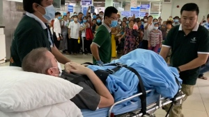 A British pilot who was Vietnam's most critical COVID-19 patient is carried on a stretcher in Ho Chi Minh city, Vietnam, Saturday, July 11, 2020. The 42-year-old man was discharged from a hospital on Saturday, less than a week after doctors said he was virus-free and healthy enough to return home to Scotland. (AP Photo/Hieu Dinh)