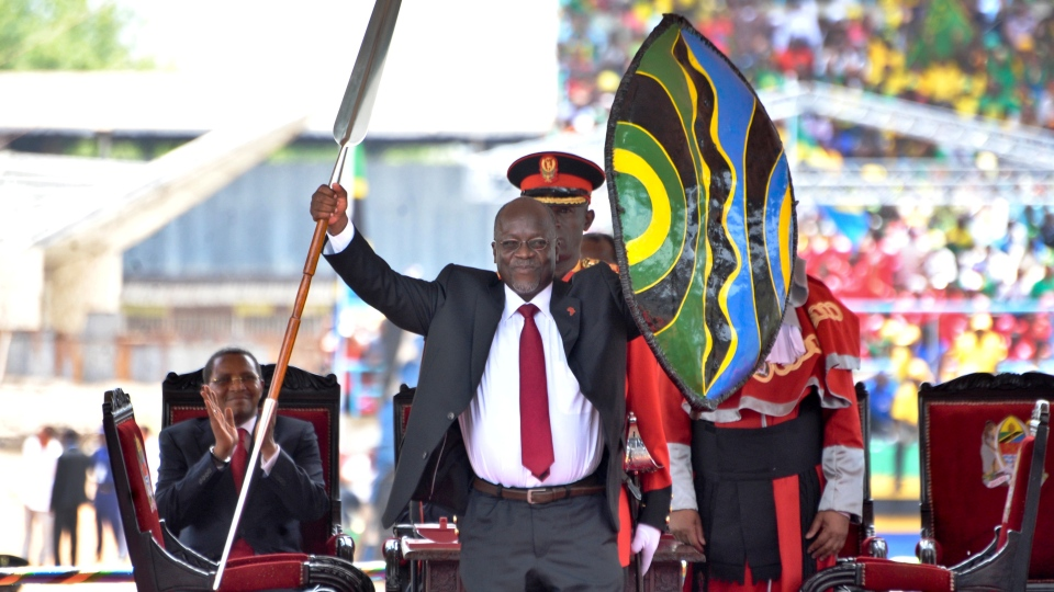 FILE - In this Nov. 5, 2015, file photo, Tanzania's President John Magufuli holds up a ceremonial spear and shield to signify the beginning of his presidency, shortly after swearing an oath during his inauguration ceremony at Uhuru Stadium in Dar es Salaam, Tanzania. As of late May 2020, the country's number of confirmed coronavirus cases hasn't changed for three weeks, and the international community is openly worrying that Tanzania's government is hiding the true scale of the pandemic. Magufuli has led a crackdown on anyone who dares raise concerns about the virus's spread or the government's response. (AP Photo/Khalfan Said, File)
