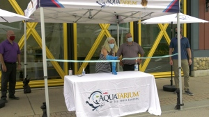 Mary-Jean McFall cuts the ribbon to reopen the Brockville Aquatarium on Saturday. (Nate Vandermeer/CTV News Ottawa)