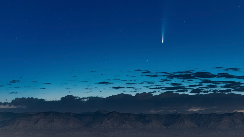 Comet Neowise soars in the horizon of the early morning sky seen from near the grand view lookout at the Colorado National Monument west of Grand Junction, Colo., Thursday, July 9, 2020. The newly discovered comet is streaking past Earth, providing a celestial nighttime show after buzzing the sun and expanding its tail. (Conrad Earnest via AP)