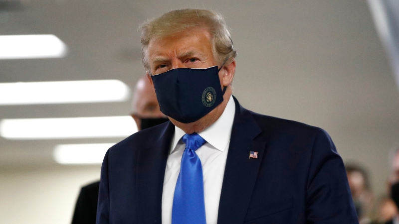 President Donald Trump wears a face mask as he walks down a hallway during a visit to Walter Reed National Military Medical Center in Bethesda, Md., Saturday, July 11, 2020. (AP Photo/Patrick Semansky)
