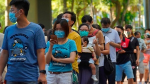 People queue up to vote in Hong Kong Sunday, July 12, 2020, in an unofficial primary for pro-democracy candidates ahead of legislative elections in September. (AP Photo/Vincent Yu)