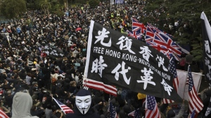FILE - In this Sunday, Jan. 19, 2020 file photo, participants wave British and U.S. flags during a rally demanding electoral democracy and call for boycott of the Chinese Communist Party and all businesses seen to support it in Hong Kong. (AP Photo/Ng Han Guan, file)