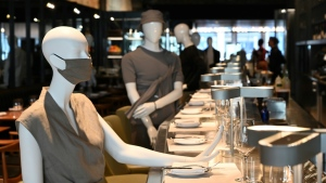 Mannequins are positioned to provide social distancing at the chic Le Monarque restaurant in Montreal on July 10, 2020; their clothes will be auctioned with proceeds going to charity. (AFP)