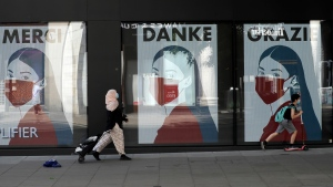 In this Thursday, May 21, 2020 file photo, a woman and child wearing face masks past a coronavirus related artwork displayed on screens in the window of the Flannels clothing store on Oxford Street, in central London. (AP Photo/Matt Dunham, file)