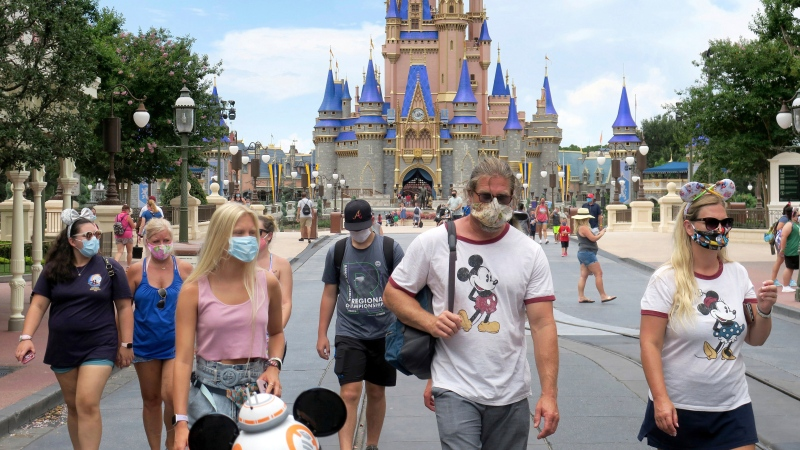 Guests wear masks as required to attend the official reopening day of the Magic Kingdom at Walt Disney World in Lake Buena Vista, Fla., Saturday, July 11, 2020. (Joe Burbank/Orlando Sentinel via AP)